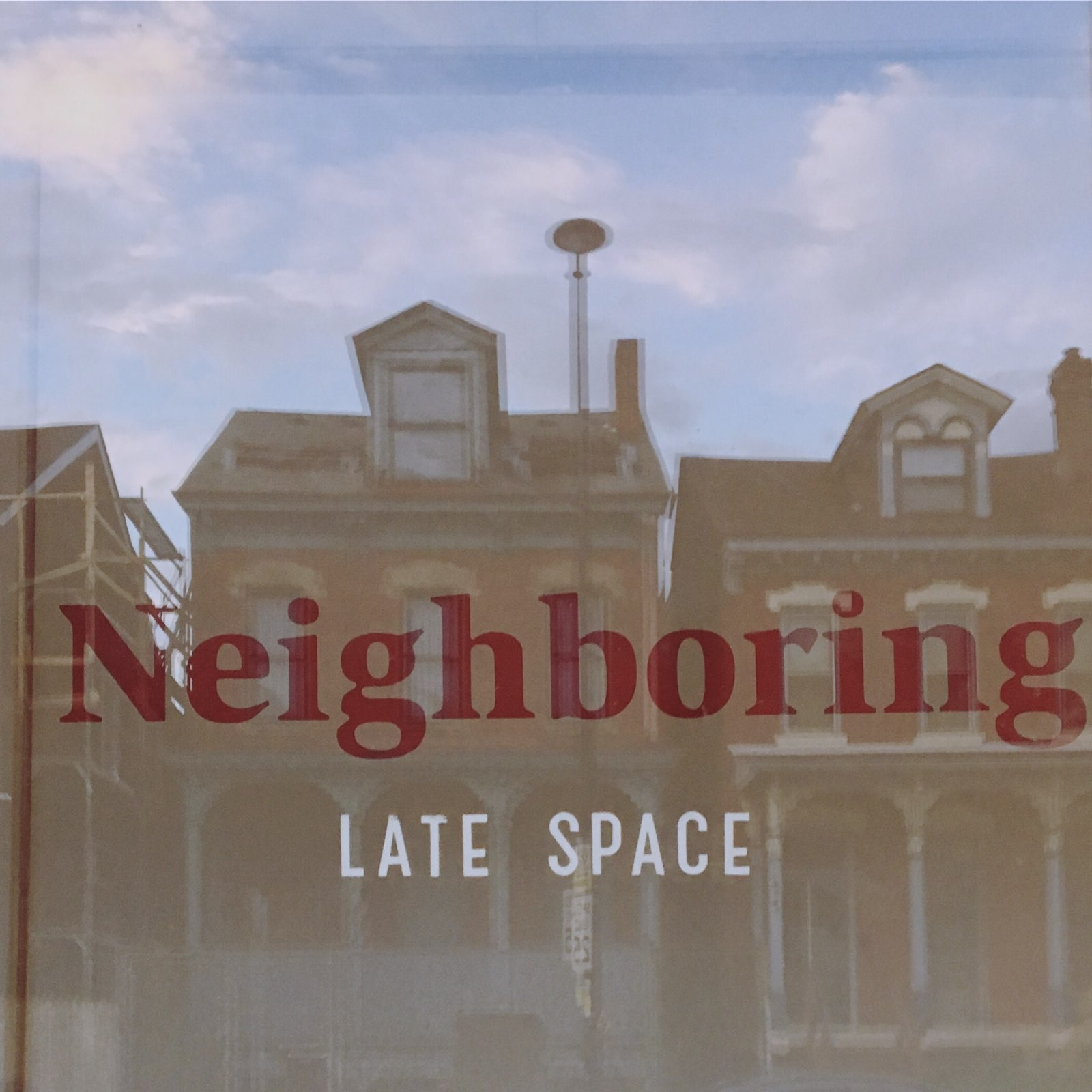 photograph of Neighboring sign through windows reflecting houses