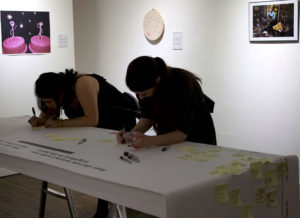 Photograph of women writing in the gallery